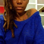 Black woman with dreadlocks wears a blue pull over