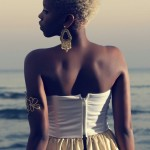 Black woman with short blond hair wears a nice dress