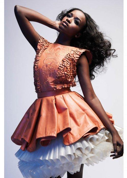 Beautiful ebony girl with long black hair wears a wonderful leather dress