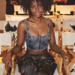 Black woman with curly hair wears a denim top and a flowing trousers
