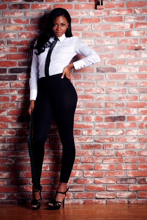 Smart ebony girl with long hair wears a white shirt and a black legging
