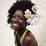 Smiling black woman has flowers in her natural hair