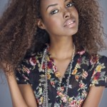 Beautiful black woman with nice natural hair wears a flowered dress