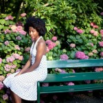 Black woman is sitting on a bench and wears a long white dress