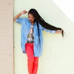 Ebony girl has long long braids and wears red pants and a blue shirt