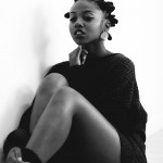 Ebony girl has a bantu knots hairstyle and just wears a pull over