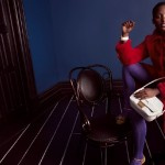 Lupita Nyong'o is wearing a red coat and purple tights. She's fashion.