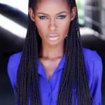 Beautiful black woman has long perfect braids and wears a blue shirt