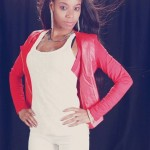 Fashion ebony girl wears a white pants, a red jacket and has long smooth hair.