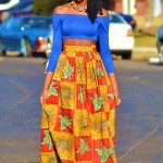 Black woman has an amazing hairstyle with locs and wears a colored long skirt and a blue top