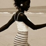 Black woman at the beach has curly hair and a stripped skirt