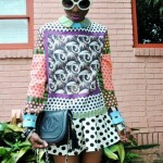 Fashion black woman wears an amazing dress, white glasses and has a bun