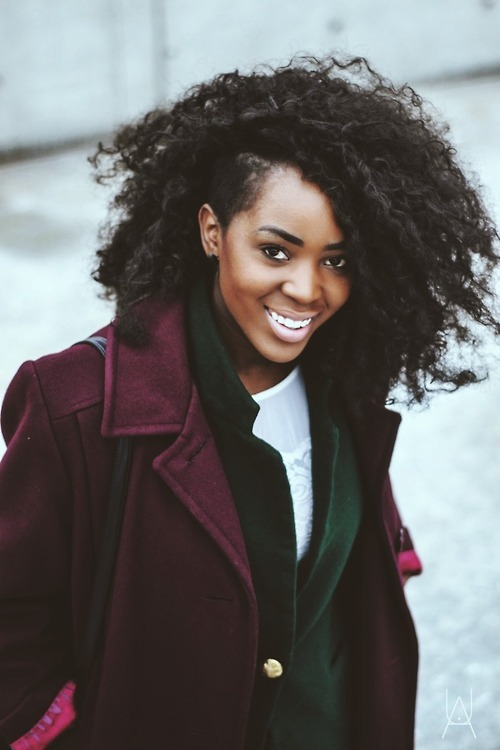 Beautiful black girl has long curly hair and wears a burgundy coat. Fashion. Hairstyle.