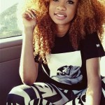 Ebony girl has a red curly hairstyle and is dressed in a streetwear style