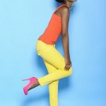 Fashion colored black woman wears an orange top, yellow pants and pink shoes