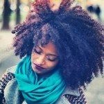 Black girl has nice curly hairstyle and wears a blue scarf