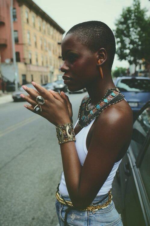 Black woman has amazing jewelry: necklace, bracelet, ring, earrings