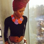 African fashion : ebony girl with colored necklace wears a red scarf, a black top and grey jeans