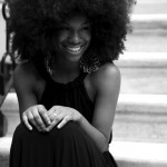 Black woman has wonderful afro hairstyle and wear a long simple dress