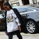Fashion street chic style. Black woman wears cool sweet shirt and class jacket