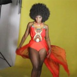 Black woman wears a red dress and has an afro hairstyle