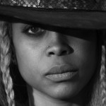 Erykah Badu with a hat and 2 blond braids