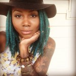 Hat, blue locs, piercing and tattoo