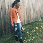 Braids hairstyle with bun, slim jeans, leather jacket