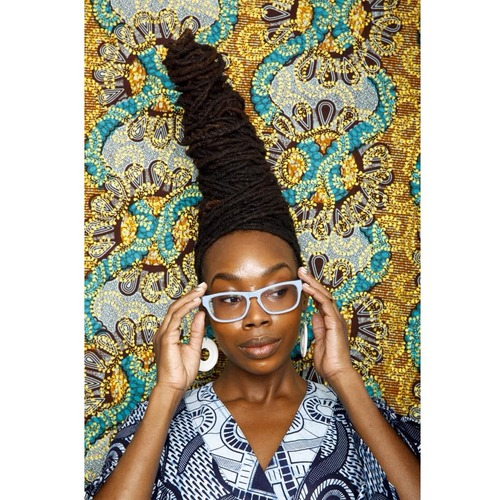 Skyscraper hairstyle with locs and white glasses