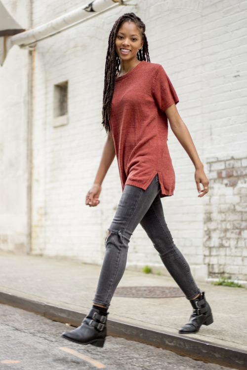 Long braids, red top, black torn jeans and boots