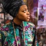 African fashion : black headscarf, flowered shirt and big necklace