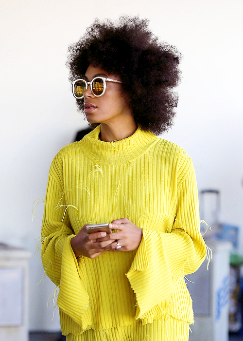 Solange Knowles dressed in yellow and natural hairstyle