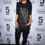 Ciara wears black leather overalls and boots