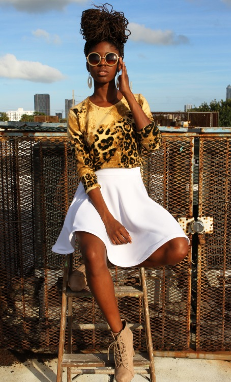 White skirt, panther top, glasses, locs hairstyle...