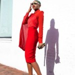 All in red : heels, skirt, shirt and sunglasses. Short green hair.