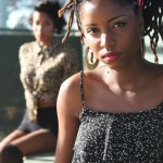 Fine locs hairstyle with red headscarf and golden earrings