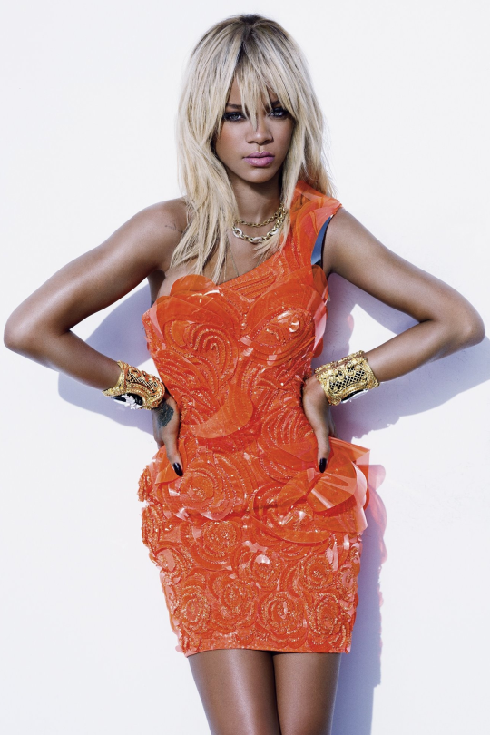 Rihanna blond hairstyle, short orange dress and big bracelets