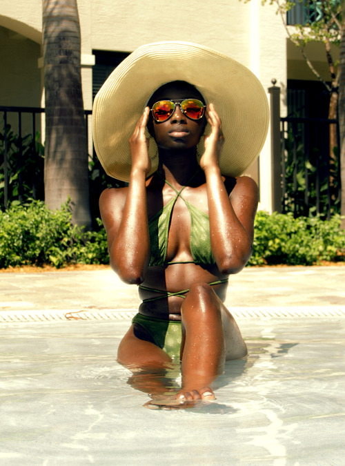 Danielle Oyewole wears nice swimsuit with sunglasses and white hat