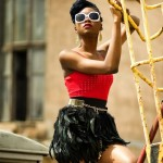 Melody Jacobs wears black feather skirt, red top and white sunglasses