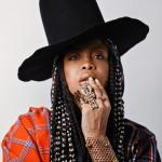 Erykah Badu braids hairstyle, black high hat, big rings, piercings